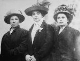 Early 20th century photo of three women in Lowell wearing elegant hats.